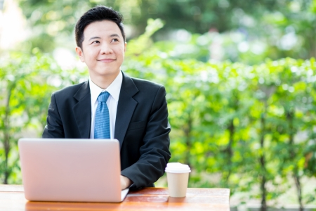 Businessman working outdoor with laptop and coffee photo