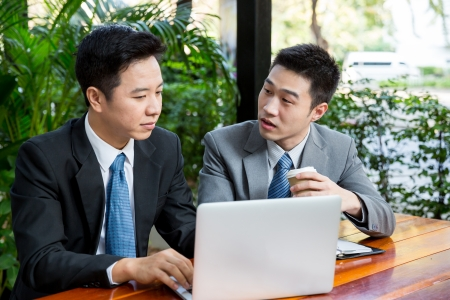 Two businessmen having a meeting while sitting in a classic coffee shop terrace, using a laptop  photo