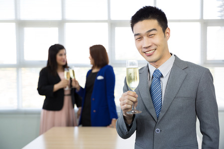 celebration of business people with champagne in a bright office photo