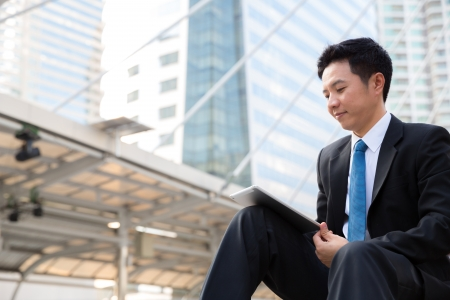 Happy young businessman using tablet outside office building photo