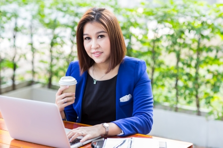 Young businesswoman working laptop with coffee photo
