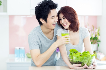 Happy Couple Cooking Together in their Kitchen at home Preparing Vegetable Salad photo