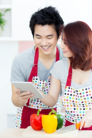 Couple in home domestic kitchen using tablet photo