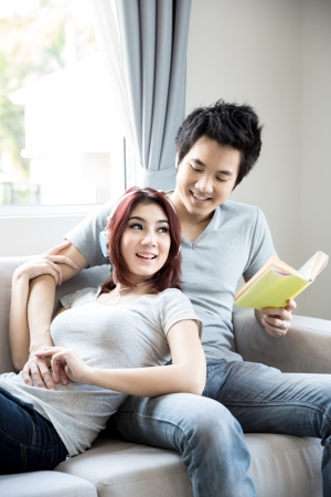 Young couple relaxing on the couch in their living room at home photo