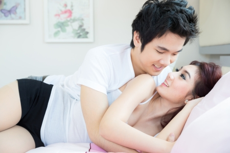 Young adult heterosexuellen Paar liegt auf dem Bett im Schlafzimmer Standard-Bild - 25039238