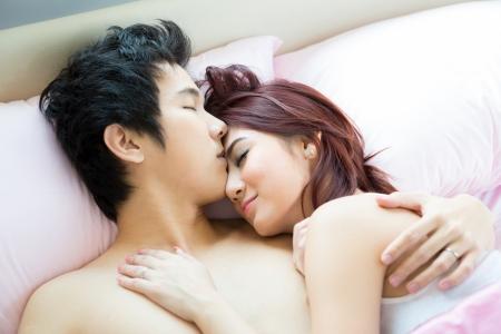 románc: Fiatal felnőtt heteroszexuális pár fekvő ágyon a hálószobában