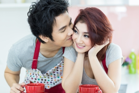 Man kissing his girlfriend with coffee in domestic kitchen