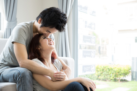 Young couple relaxing on the couch in their living room at home