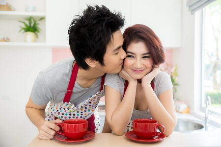 Man kissing his girlfriend with coffee in domestic kitchen photo