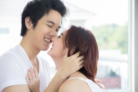 happy asian couple: Young adult heterosexual couple lying on bed in bedroom