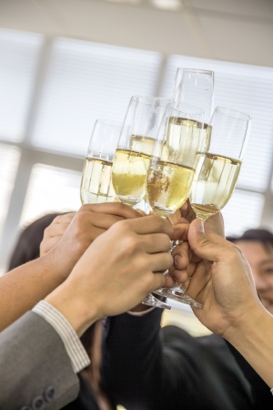 celebration of business people with champagne in a bright office