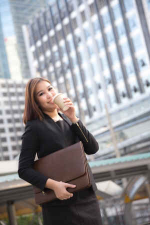 Smiling businesswoman with a cup of coffee against building photo