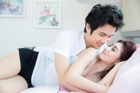 románc: Fiatal felnőtt heteroszexuális párosít, fekvő ágyon a hálószobában Stock fotó