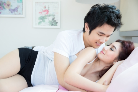 Mladý dospělý heterosexuální pár ležící na posteli v ložnici Reklamní fotografie