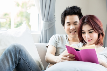 Young couple reading a book on the sofa in their living room at home photo