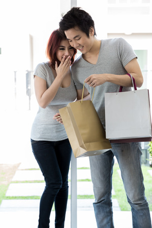 Young couple with shopping bags in their living room at home photo