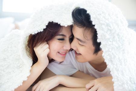 parejas de jovenes: Joven pareja heterosexual adulta acostado en la cama en el dormitorio