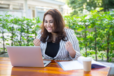Young businesswoman working laptop with coffee and celebrate her work photo
