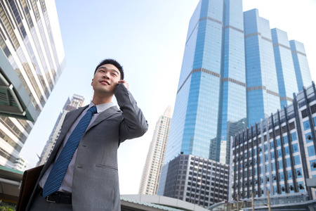 Smiling businessman using mobile phone against building photo