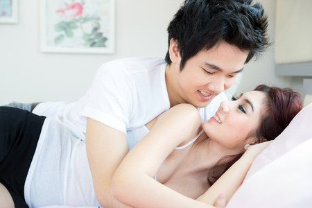 asian wife: Young adult heterosexual couple lying on bed in bedroom