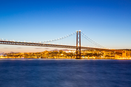 Lisbon cityscape and the 25 de Abril Bridge, Portugal at dusk photo