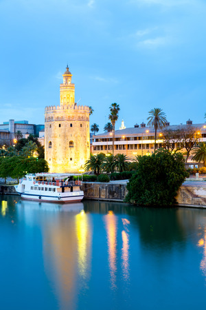 Golden Tower with cityscape and river of Sevilla at night Seville, Spain