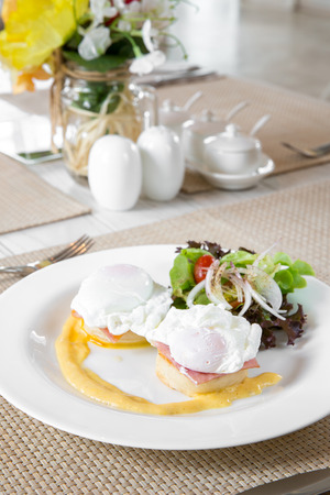 Eggs Benedict- toasted English muffins, ham, poached eggs, and delicious buttery hollandaise sauce for breakfast photo