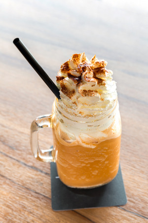 whipping: glass of Ice milk tea with Whipped Cream Stock Photo