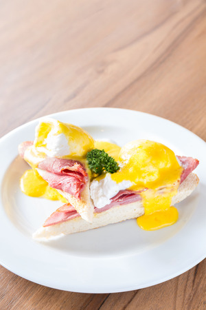 buttery: Eggs Benedict breakfast- toasted English muffins, ham, poached eggs, with buttery hollandaise sauce