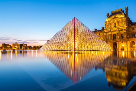 Paris  June 18: Louvre museum at dusk on June 18 2014 in Paris. This is one of the most popular tourist destinations in France displayed over 60000 square meters of exhibition space.. Editorial