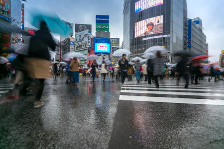 implementations: TOKYO  FEB 18: Pedestrians cross at Shibuya Crossing on Febuary 18 2015 in Tokyo Japan. The crosswalk is one of the worlds most famous implementations of a scramble crosswalk.
