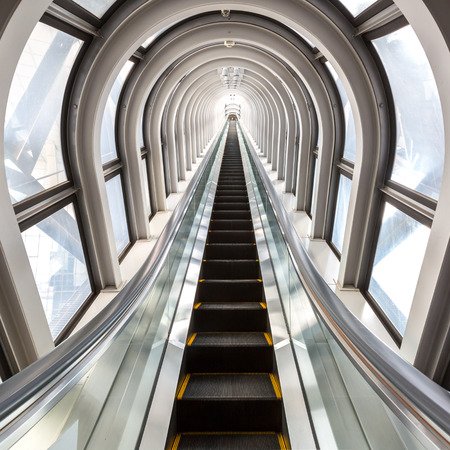 perspective escalators stairway inside contemporary blue glass business centre concept of successful career elevation photo