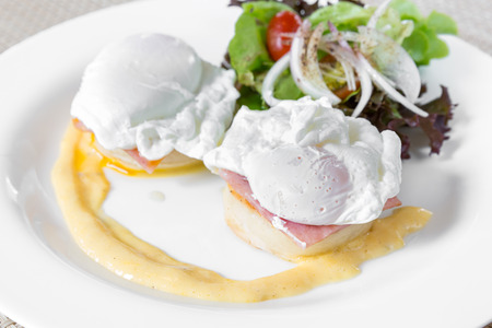 uk cuisine: Eggs Benedict- toasted English muffins, ham, poached eggs, and delicious buttery hollandaise sauce for breakfast Stock Photo