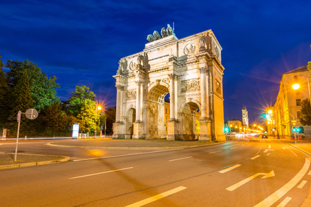 triumphal: The Siegestor Victory Arch in Munich at dusk with traffic going around the arch.