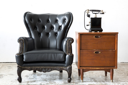 old vintage: Black genuine leather classical style chair with side cabinet and telophone Stock Photo