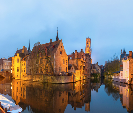 patronage: Historic medieval buildings along a canal in Bruges, Belgium at dusk.