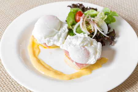 buttery: Eggs Benedict- toasted English muffins, ham, poached eggs, and delicious buttery hollandaise sauce for breakfast Stock Photo