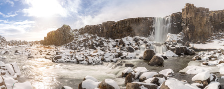 drifting ice: Oxararfoss Waterfall in the winter in pingvellir valley National Park in Iceland panorama
