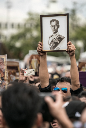 BANGKOK, Thailand - OCT 22: Unidentified people lift His Majesty King Bhumibol Adulyadej photo on October 22,2016 Bangkok, Thailand. Thailands King, the worlds longest-reigning monarch, has died after 70 years as head of state.