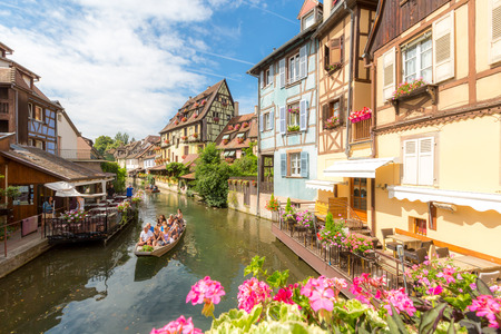considers: COLMAR - JUL 13: Unidentified tourists riding boat in La Lauch at La Petite Venise on July 13, 2015. Colmar is situated on the Alsatian Wine Route and considers itself to be the capital of Alsatian wine
