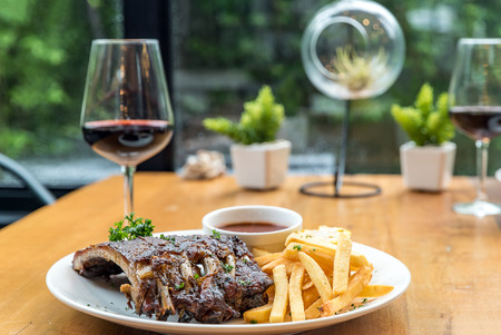 Grilled Barbecued Pork Baby Back Ribs grilled sweet corn and fries on dining table with red wine Stock Photo