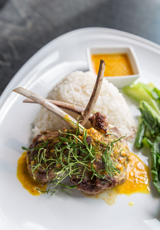 sause: Grilled Lamb steak with spicy yellow sause and green vegetable on jasmine rice.