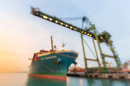 Blurred abstract background of Industrial port with container ship at dusk Stock Photo