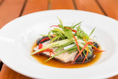 Steamed sea bass fillet with soy sauce and leek in olive linseed oil