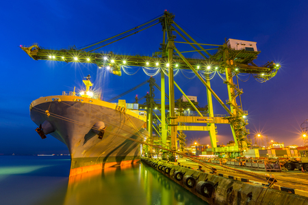Industrial port with container ship at dusk Stock Photo