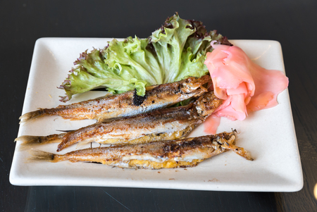 grilled shishamo on white plate