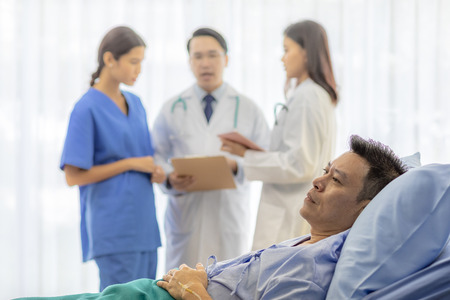 Worried patient in bed with professional team doctors in background Stock Photo