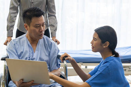 Physical therapist explain treatment method to senior patient and relative using notebook