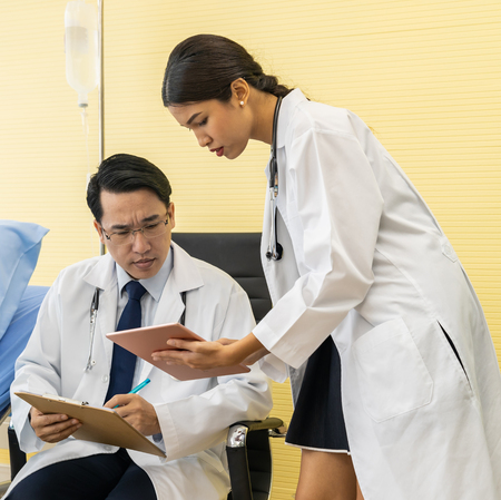 Two Asian Doctors make discussion while routine health check with patient in hospital ward
