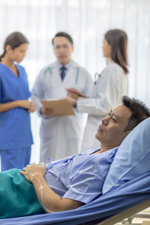 Worried patient in bed with professional team doctors
